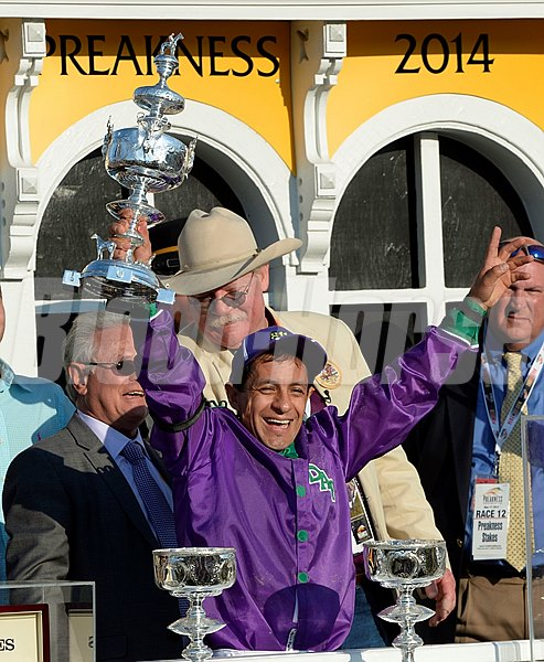 Jockey Victor Espinoza holds the winner's trophy aloft after winning the Preakness aboard California Chrome.