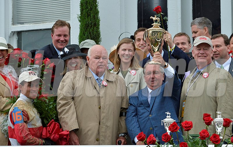 "Trainer Shug McGaughey holds the winner's trophy after Orb won the 139th running of the Kentucky Derby May 4, 2013 at Churchill Downs in Louisville, Kentucky.  He is flanked by co-owners Ogden Mills ""Dinny"" Phipps, second from left and Stuart Janney, right and jockey Joel Rosario on the left."
