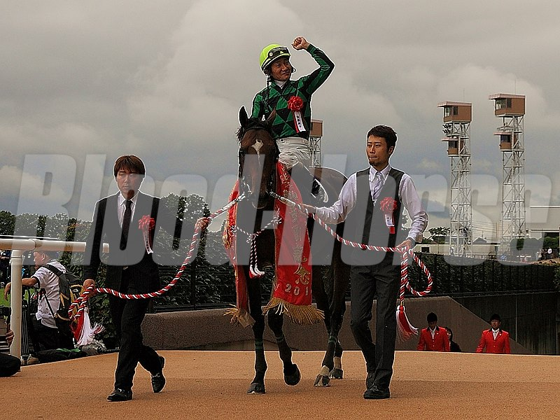 Jockey Yoshitomi Shibata celebrates after Just A Way's victory in the Yasuda Kinen.