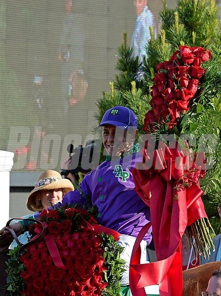 Jockey Victor Espinoza raises his roses in the Churchill Downs winners circle.