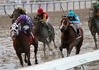 Jamie Theriot (purple cap) aboard Max Me Out holds off challengers to win the 24th running of the Woodchopper Stakes at Fair Grounds.