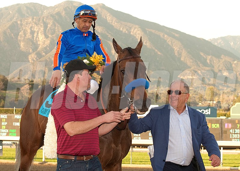 "Co-owner Bernie Schiappa, right, leads Game On Dude and Mike Smith into the winner's circle after victory in the Grade I $750,000 Santa Anita Handicap Saturday, March 2, 2013 at Santa Anita Park, Arcadia CA.  The ""Dude"", trained by Bob Baffert, also won the 2011 running of the Big 'Cap. 