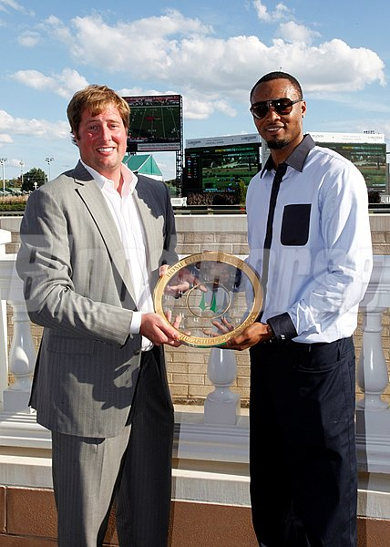 Rashard Lewis accepts the trophy after Cigar Street's victory in the Homecoming Classic Stakes at Churchill Downs in 2014.