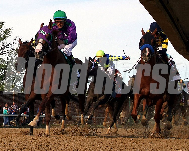 California Chrome and Victor Espinoza come off the final turn with the lead.