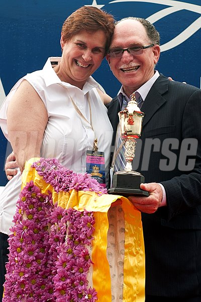 Toronto Ont.July 7,2013.Woodbine Racetrack.Trainer Nick  and Marth Gonzalez hold ther Queen's Plate trophy after Midnight Aria captures the Queen's Plate Stakes. michael burns photo