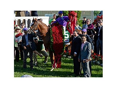 Jose Espinoza (right, gray suit) joined his brother Victor in the Kentucky Derby Winner's Circle.