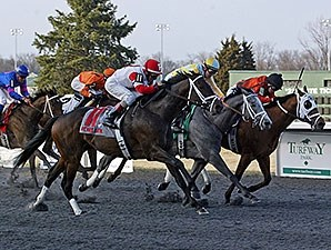 We Miss Artie (left) comes on late to take the Spiral Stakes at Turfway.