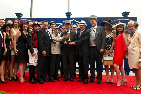 Toronto Ont.July7,2013.Woodbine Racetrack.Queen's Plate Stakes.His Excellency the Governor General of Canada David Johnston present the Queen's Plate trophy to Tucci Stables after Midnight Aria ridden by Jockey Jesse Campbell captures the 154th running of the Plate. michael burns photo