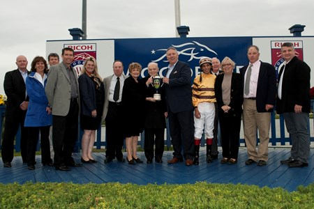 The Ricoh Woodbine Mile presentation. The trophy is presented by Pete Ronan, center, to Mr. Morton Fink.