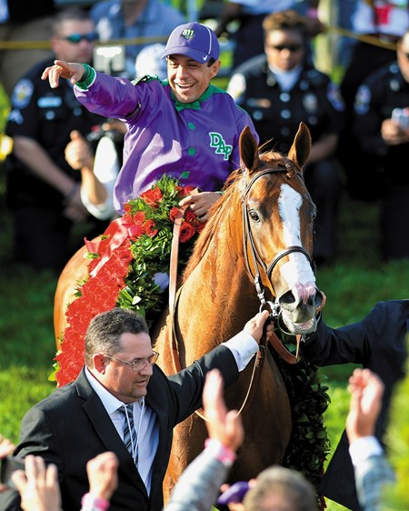 California Chrome and Victor Espinoza are adorned with roses after winning the Kentucky Derby.