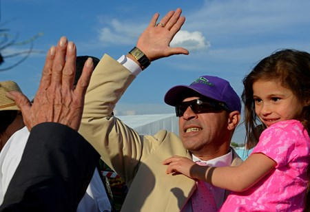 Exercise rider Willie Delgado high fives after California Chrome wins the Preakness.