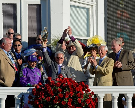 Trainer Art Sherman holds up the Kentucky Derby trophy.