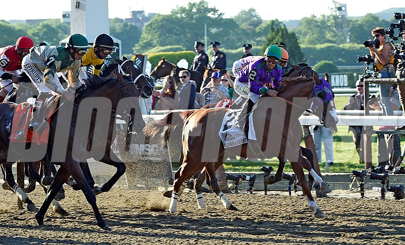 California Chrome (#2), with jockey Victor Espinoza, moves toward the lead early in the Belmont Stakes.
