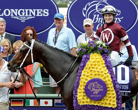 Untapable and jockey Rosie Napravnik are adorned with flowers after winning the Grade I Breeders' Cup Distaff.