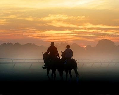 Trainer Dallas Stewart works as the sun rises on another morning at the Oklahoma training track.