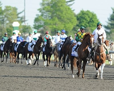 The post parade heads towards the starting gate for the Blue Grass Stakes.