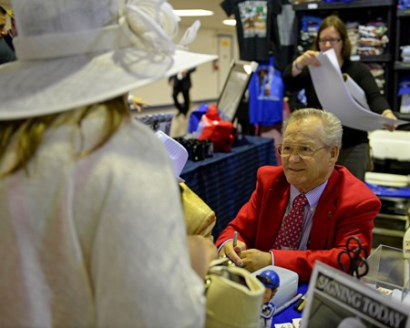 Caption: Ron Turcotte signing autographs and talking with fans at Secretariat booth.