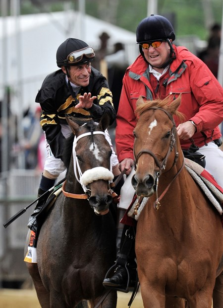 Oxbow gets a pat on the head while heading to the winners' circle, after winning the Preakness...