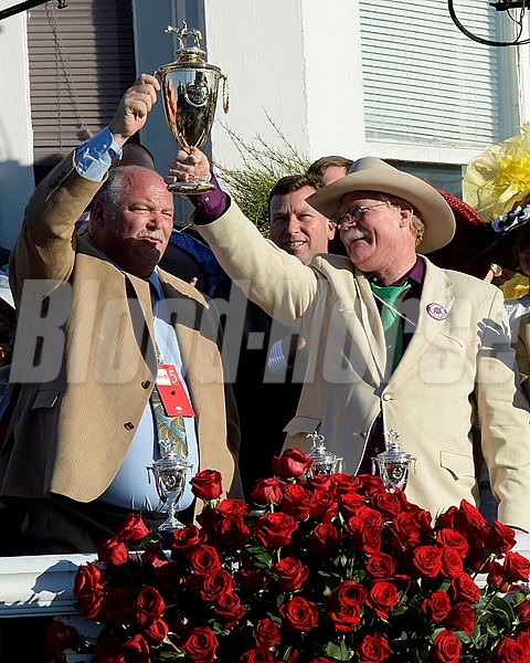 Owners Perry Martin and Steve Coburn hold the Kentucky Derby trophy in the winners circle after California Chrome wins the Kentucky Derby.