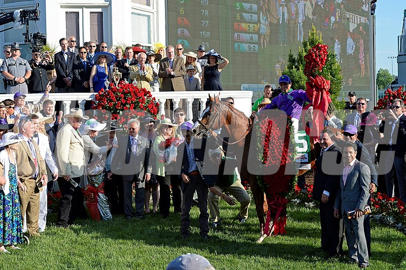 The connections of California Chrome pose with their champion in the winners circle, celebrating their Kentucky Derby win.