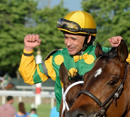 Mike Smith raises his fists to celebrate his win in the third jewel of the triple crown.