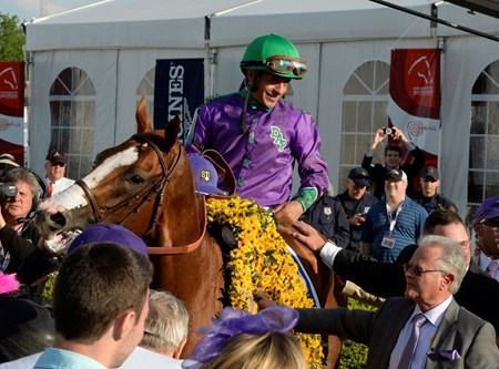 California Chrome and jockey Victor Espinoza receive the winner's blanket of flowers with trainer Art Sherman.