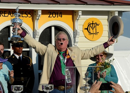 Owner Steven Coburn holds the winner's trophy in the air after California Chrome won the Preakness Stakes.