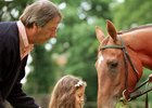 Trainer Henry Cecil is at hand as Princess Reema feeds grass to her father Prince Fahd Salman's Oaks winning filly Ramruma, named after her, at Newmarket June 21, 1999.