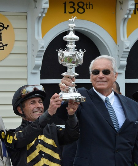 Gary Stevens and trainer D. Wayne Lukas hold the winner's trophy after Oxbow with Gary Stevens aboard won the 138th running of the Preakness Stakes at Pimlico in Baltimore, Maryland May 18, 2013.