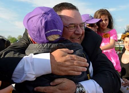 Assistant trainer Alan Sherman hugging a California Chrome team member after the win.