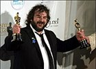 Peter Jackson, director and screenwiter of 'The Lord of the Rings: The Return of the King,' holds up Oscar awards for best director and best picture.