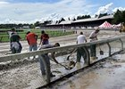 NYRA Track workers remove standing water and level out the track after torrential rains caused damage to the Saratoga race course.