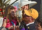 Doug O'Neill kissing the Kentucky Derby trophy.