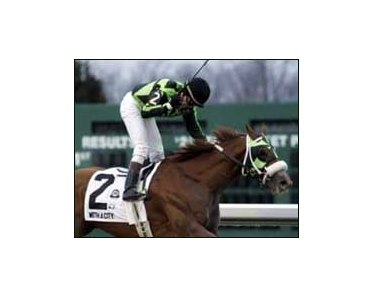 Jockey Brice Blanc celebrates atop With a City as they cross the finish line first in the Lane's End Stakes, Saturday at Turfway Park.