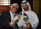 American trainer Bob Baffert (left) and Godolphin Racing's trainer, Saeed bin Suroor, hold falcons used in Wednesday's Dubai World Cup post position draw.