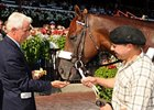 Commentator enjoys cake at his retirement party at Saratoga.