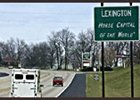 "A horse van passes by a sign near Lexington proclaiming the city the ""Horse Capital of the World."""