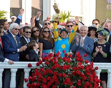 Victor Espinoza triumphantly raises the trophy in the winner's circle at Churchill Downs.