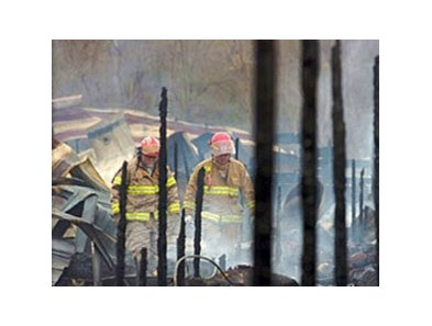 Firemen investigate the remains of a horse barn at Riverside Downs.