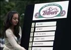 New York Racing Association's Lisa Fiorillo hangs the names of horses during the Travers Stakes post position draw.