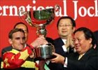 Ronald Arculli, chairman of the Hong Kong Jockey Club, presents a silver whip and the cash prize to jockey Andrasch Starke, winner of the Cathay Pacific International Jockeys' Championship 2005.