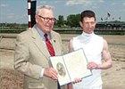 Pennsylvania Racing Commission chairman F. Eugene Dixon, left, presents Stewart Elliott with the Proclamation that Saturday, May 1, 2004 is Smarty Jones Day at both Philadelphia Park and Penn National.