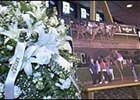 Flowers sit next to a photograph of late jockey Michael Rowland at Turfway Park.