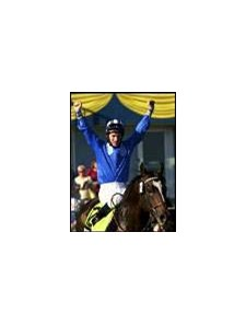 Jockey Richard Hills raises his arms in celebration after riding Mutamam to win the Canadian International.