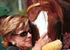 Trudy McCaffery hugs Bienamado after he won the 2001 Charles Whittingham Handicap.