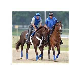 Smarty Jones, left, and his pony, Butterscotch, take a turn around the track Friday morning.