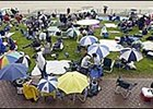 Early arrivals at Belmont Park used umbrellas to protect themselves from rain.