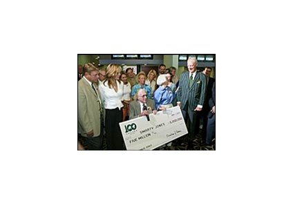 Oaklawn Park president Charles Cella, right, presenting Roy and Pat Chapman with an oversized copy of the bonus check won by Smarty Jones.