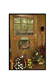 A photo and flowers, including roses, black-eyed susans, and carnations, adorn the stall door where Seattle Slew resided.
