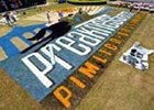 Workers paint the Preakness logo on the infield grass at Pimlico Racecourse.